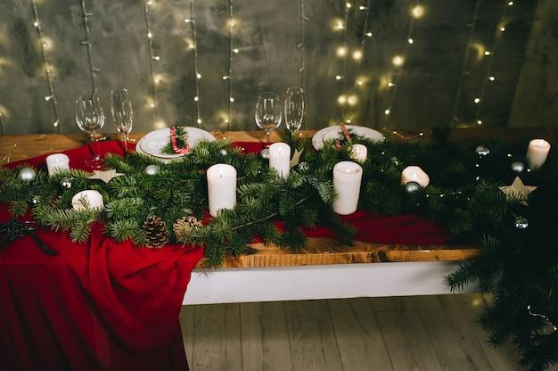 Cadre de table rouge élégant avec des bougies allumées et des décorations de noël sur une surface grise