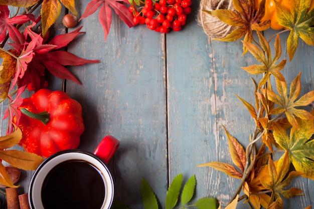 Cadre avec une tasse de café avec des feuilles d'automne et petites citrouilles
