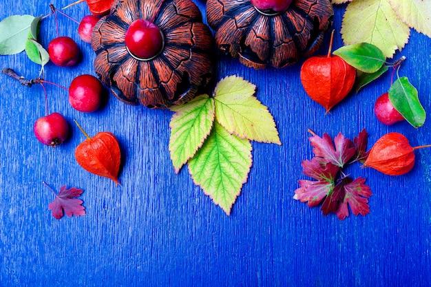 Cadre de thanksgiving day. feuilles, citrouille et petite pomme autour de bois bleu rustique