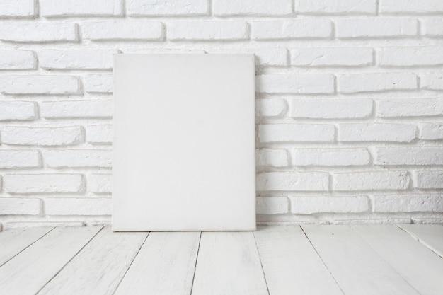 Cadre de toile blanche vide sur une table en bois