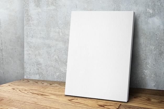 Cadre de toile blanche vierge appuyé au mur de béton et plancher de bois