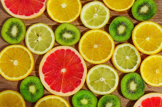 Cadre avec une tranche d'oranges, citrons, kiwis, motif de pamplemousse isolé.