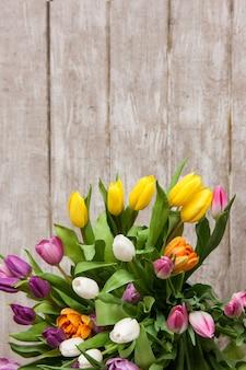 Cadre de tulipes à fleurs colorées. fond floral. gros bouquet de printemps sur fond en bois avec fond. mariage, cadeau, anniversaire, 8 mars, pâques, concept de carte de voeux pour la fête des mères