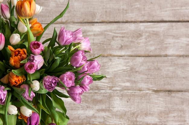 Cadre de tulipes à fleurs roses. fond floral. bouquet de printemps sur fond en bois avec fond. mariage, cadeau, anniversaire, 8 mars, concept de carte de voeux fête des mères