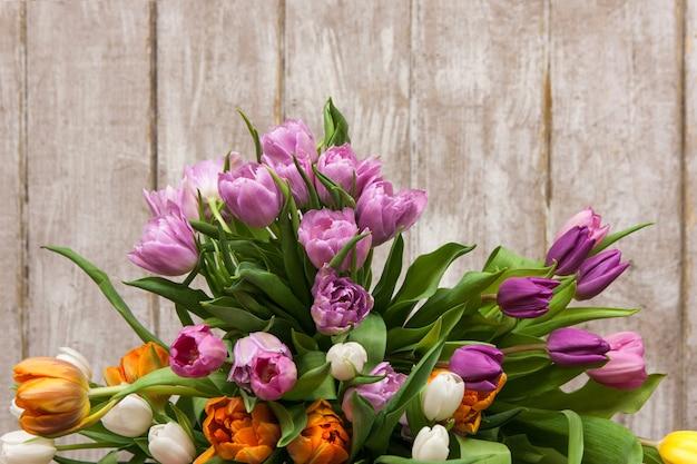 Cadre de tulipes à fleurs roses. fond floral. gros bouquet de printemps sur fond en bois avec fond. mariage, cadeau, anniversaire, 8 mars, pâques, concept de carte de voeux pour la fête des mères