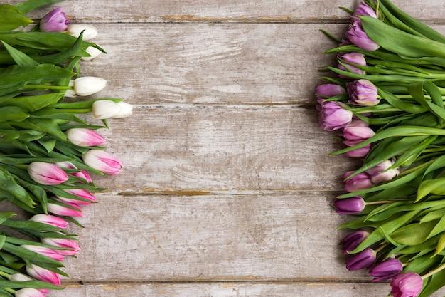 Cadre de tulipes roses. fond floral. bouquet de fleurs de printemps sur fond en bois avec fond. mariage, cadeau, anniversaire, 8 mars, concept de carte de voeux fête des mères
