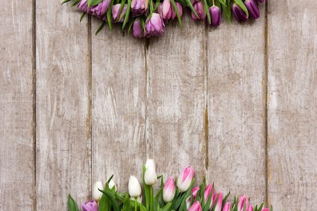 Cadre de tulipes roses. fond de printemps. bouquet de fleurs sur fond en bois avec fond. mariage, cadeau, anniversaire, 8 mars, concept de carte de voeux fête des mères