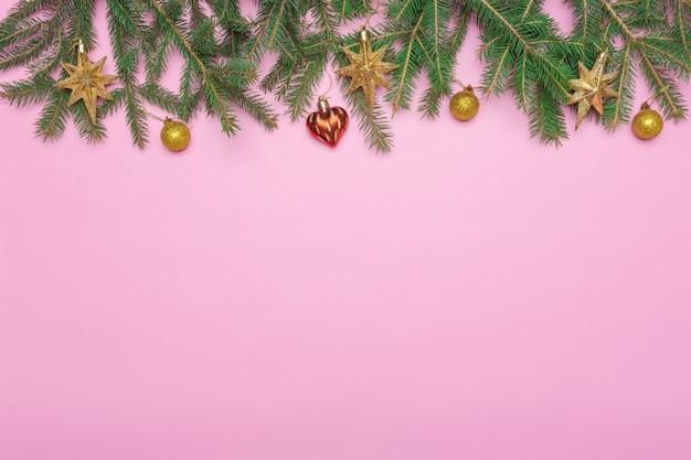 Cadre de vacances de décorations de noël sur fond rose avec une branche de sapin