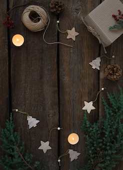 Cadre vert de noël de branches d'arbres frais, bougies allumées, jouets de noël en bois sur des planches vintage. concept d'écologie. carte de noël vierge.