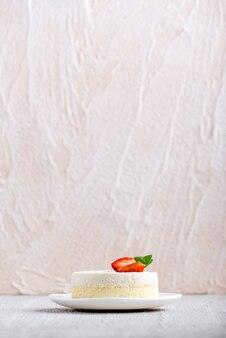 Cadre Vertical. Cheesecake Aux Fraises Sur Plaque Blanche Sur Fond Clair. Vue De Côté. Photo Premium