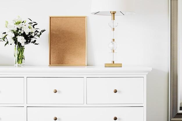 Cadre vertical doré et bouquet de fleurs fraîches sur des meubles blancs, décoration et design de luxe pour la maison ...