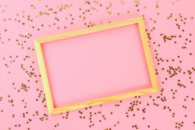Un cadre vide en bois sur un fond pastel entouré d'étoiles et de boules décoratives brillantes.