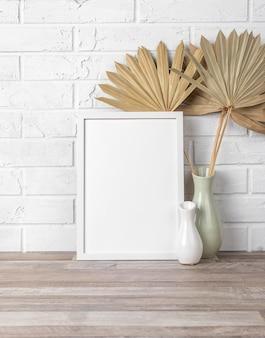 Cadre vide sur une étagère à côté du vase