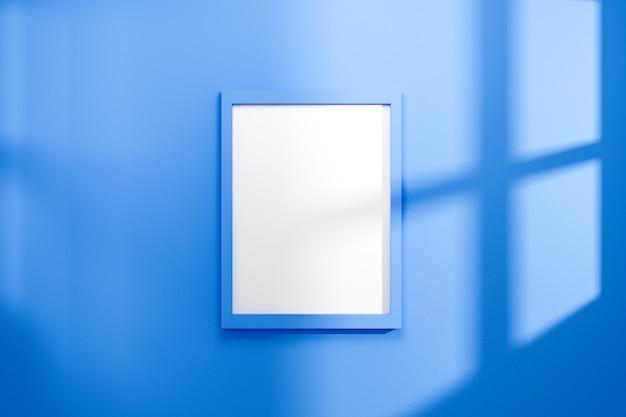Cadre vide sur fond de mur bleu vif avec la lumière naturelle de la fenêtre.