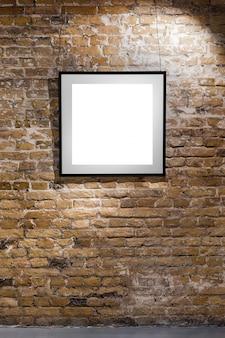 Cadre vide sur le mur de briques claires. affiche d'espace vide ou cadre d'art en attente d'être rempli. cadre carré noir