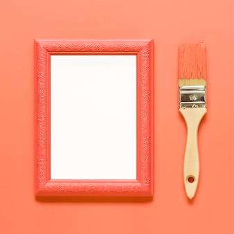 Cadre vide orange et pinceau en bois