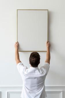 Cadre vierge accroché par un jeune homme sur un mur blanc minimal