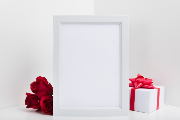 Cadre vierge avec boîte-cadeau et roses rouges