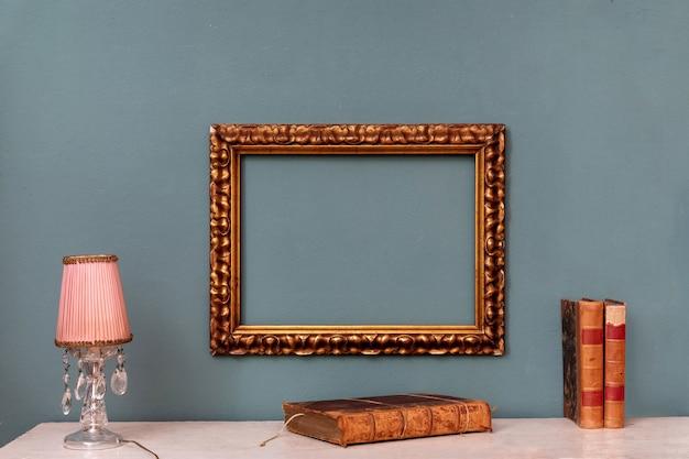 Cadre vintage rectangulaire or vide suspendu à un mur vert