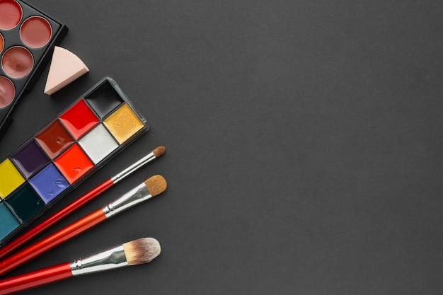 Cadre de vue au-dessus avec pinceau à maquillage et palettes