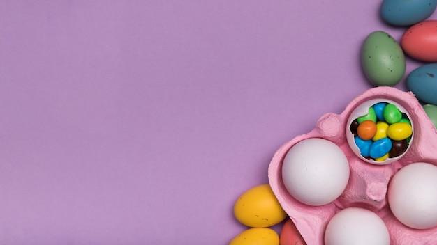 Cadre vue de dessus avec des bonbons dans une coquille d'oeuf