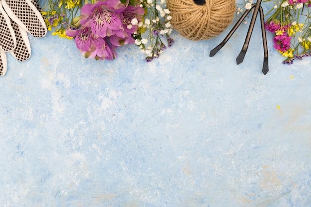 Cadre vue de dessus avec des fleurs et des outils