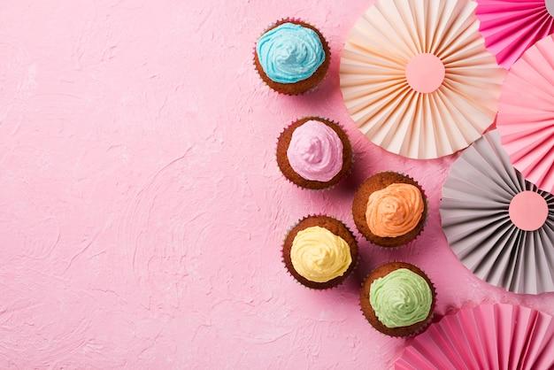Cadre vue de dessus avec des muffins glacés sur fond rose