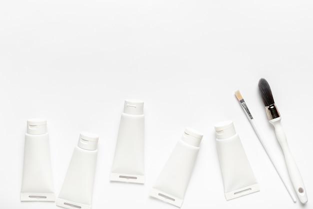 Cadre vue de dessus avec tubes de peinture et pinceaux