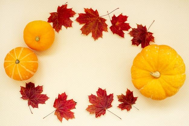 Cadres d'automne lumineux pour les citrouilles orange de la carte de saison et les feuilles d'érable rouge avec fond