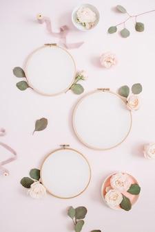 Cadres de broderie avec boutons de fleurs roses beiges et eucalyptus sur fond rose pastel pâle. mise à plat, vue de dessus