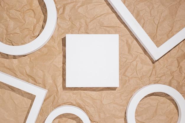 Cadres carrés de podiums blancs pour présentation sur fond marron kraft froissé. vue de dessus, mise à plat.
