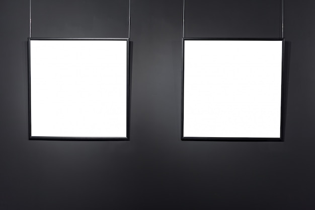 Cadres carrés vides sur le mur de briques noires. affiches d'espace vide ou cadre d'art en attente d'être rempli. fond de cadre noir carré