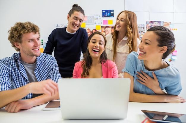 Cadres discutant sur un ordinateur portable au bureau