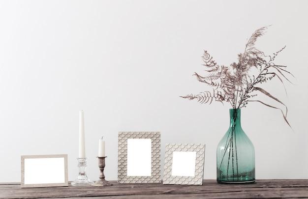 Cadres et fleurs séchées dans un vase sur une vieille étagère en bois
