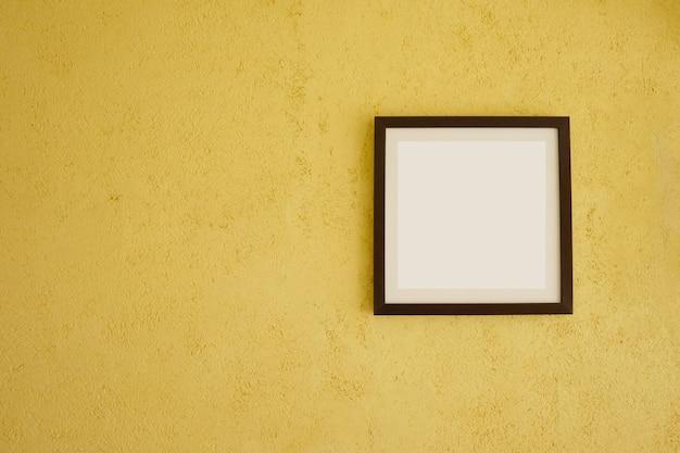 Cadres d'images vides sur les murs jaunes vintage.