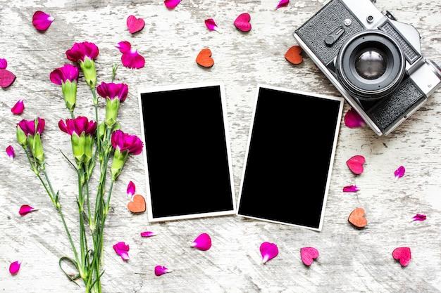 Cadres photo vierges, appareil photo rétro vintage et fleurs d'oeillets violets