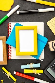 Des cadres photo vue de dessus avec des crayons colorés sur un dessin de fond sombre inspirent le cahier de stylo bloc-notes scolaire