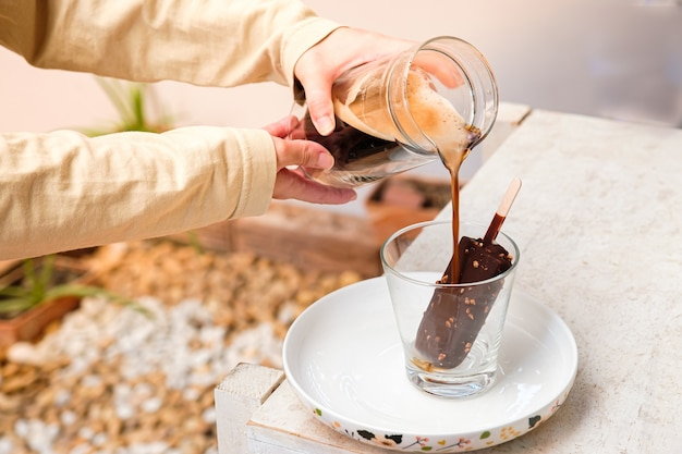 Café affogato avec glace au chocolat pop sur une tasse en verre