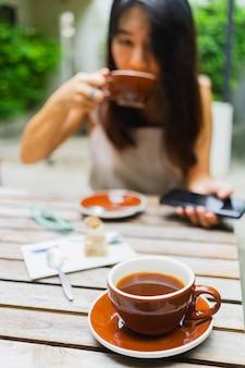 Café americano chaud dans la tasse avec femme asiatique boire un café dans le café.