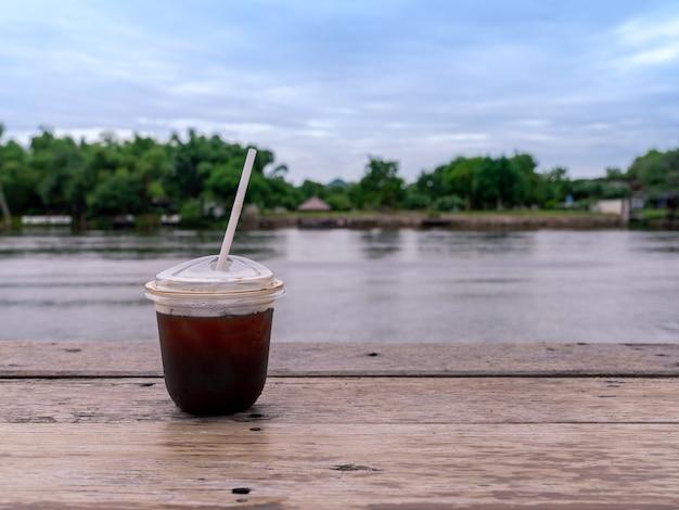Café americano glacé dans une tasse transparente à emporter sur une table en bois avec vue sur la rivière calme et fraîche