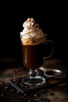 Café arabica chaud noir avec de la crème et de la cannelle dans un verre en verre sur un fond sombre