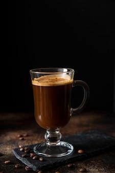 Café arabica chaud noir avec de la mousse dans un verre en verre sur fond sombre