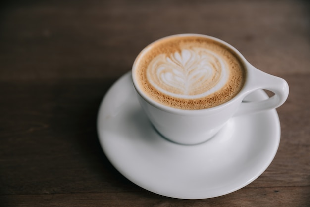 Café art cappuccino ou latte à base de lait sur la table en bois du café