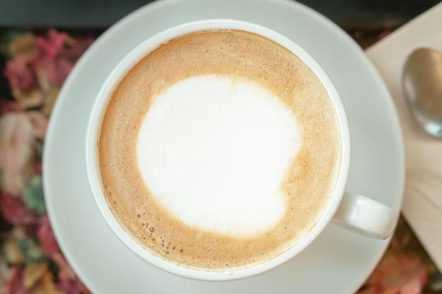 Café d'art latte chaud dans une tasse blanche avec une cuillère en métal arrière-plan flou