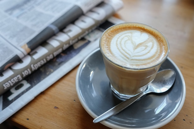 Café d'art latte avec journal sur table en bois