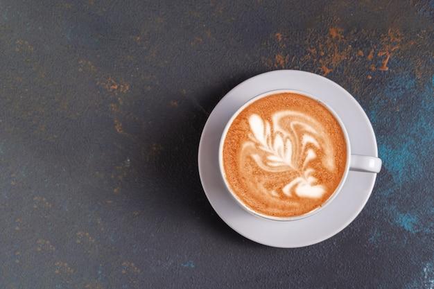 Café d'art latte à plat avec de la mousse dans une tasse sur bleu