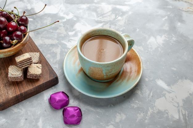 Café au lait avec des bonbons gaufres et cerises sur un bureau gris clair