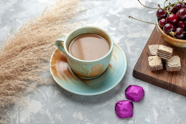 Café au lait avec des bonbons gaufres et des cerises sur la lumière