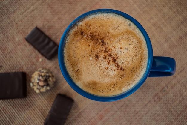 Café au lait et à la cannelle dans une tasse bleue avec du chocolat