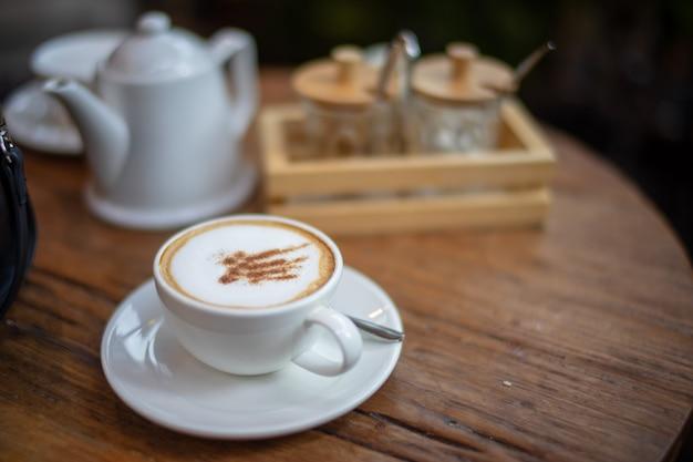 Café au lait cappuccino dans une tasse blanche sur une table en bois avec un arrière-plan flou.